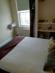 Another photo of my hotel bed partly showing but angled to show part of the room with the window that overlooks the road the hotel is on