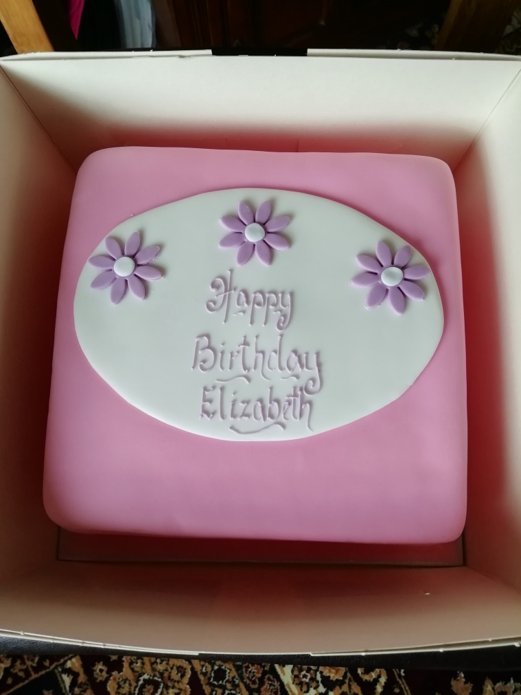 Pink birthday cake with lilac flowers icing, with words Happy Birthday Elizabeth