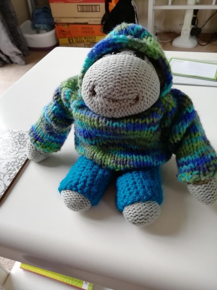 Bob the toy chimp, wearing a green and blue knitted jumper and blue knitted trousers