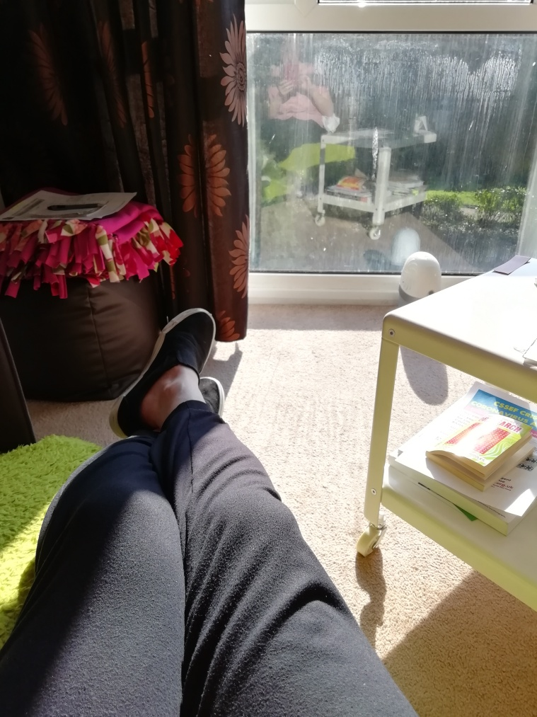 My legs showing in photo while gaving them up on the settee, looking outside at the sunny weather