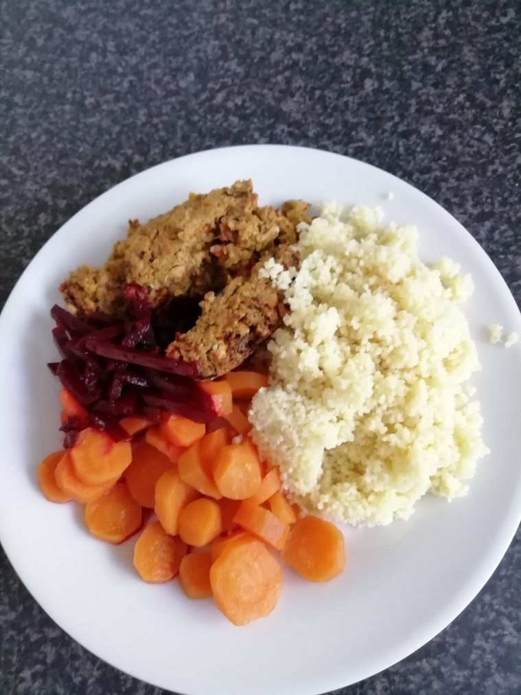 Cous cous, carrots, beetroot and nut roast on a white dinner plate