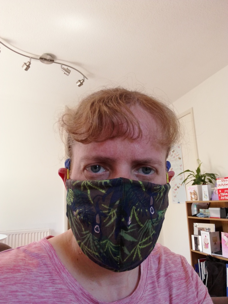 Face mask. The design has leafs and monkeys on it. Colours in greens, brown and blue.