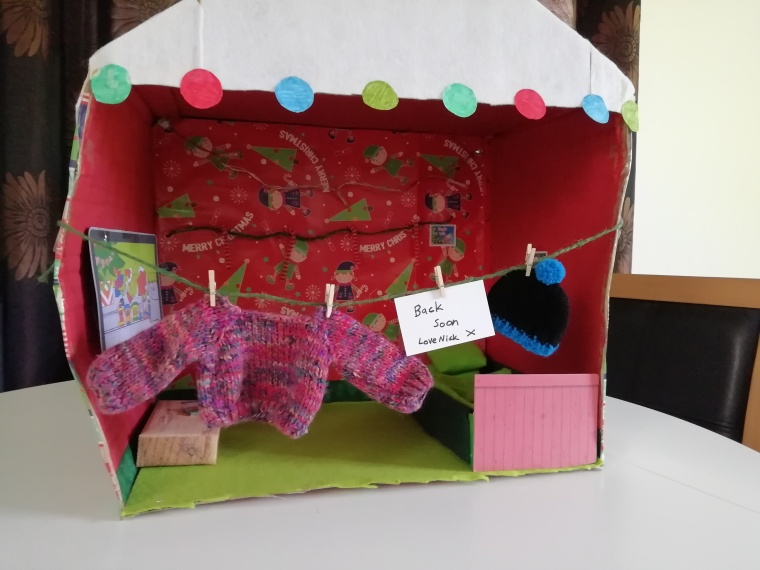 Nick the elfs home which he's not home at the moment. A sign saying back soon. The house has one room. His bedroom is here and tv and dvd player. Clothes are on washing line.