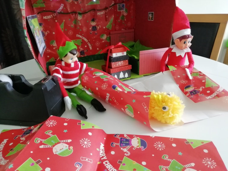 Nick and Noel wrapping presents. A pom pom chick is partly wrapped.