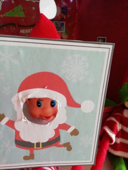 Noel poking his face through a cut out face santa picture
