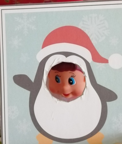 Noel sticking his face through a cut out face penguin picture