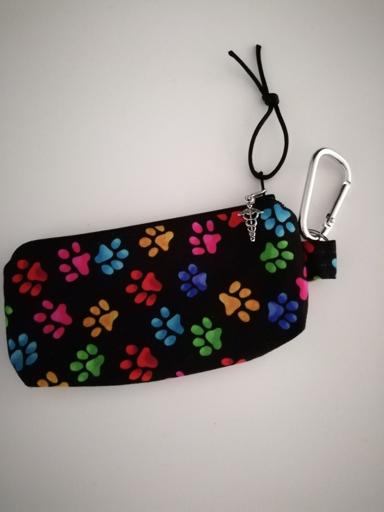 Zipped pouch. Black, with colourful paw prints on it.